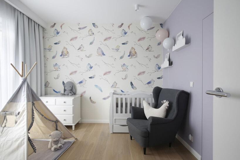 pokój dla dziewczynki zjedną lekko fioletową ścianą obok białej ściany ztapetą zrysowanymi ptakami