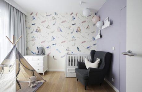 pokój dla dziewczynki z jedną lekko fioletową ścianą obok białej ściany z tapetą z rysowanymi ptakami