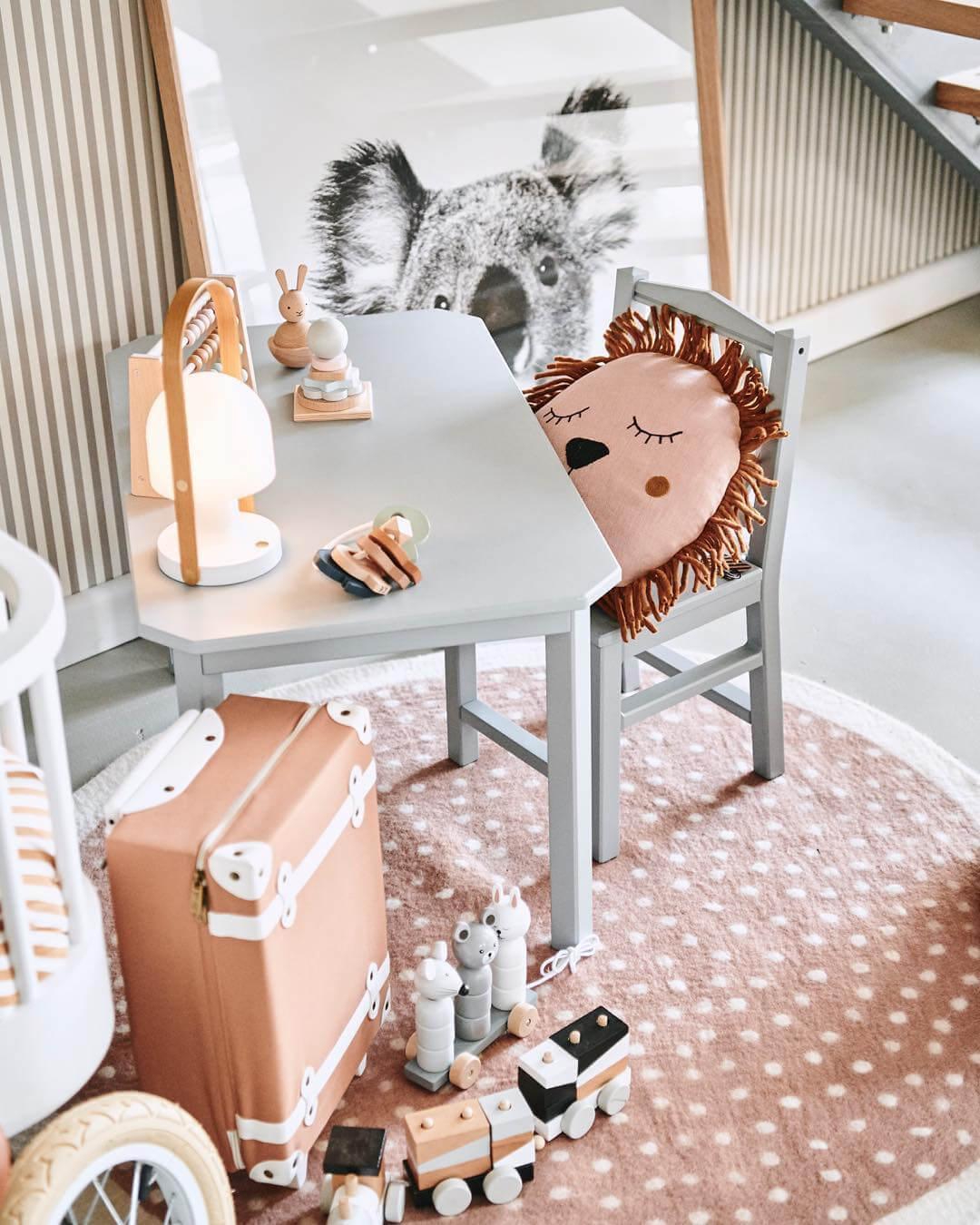 mały biały stolik ikrzesło zokrągłą poduszką lwa zkredkami ilampą na stoliku