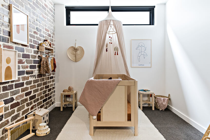 pokój dla niemowlaka zdrewnianym łóżeczkiem zbaldachimem pod sufitem
