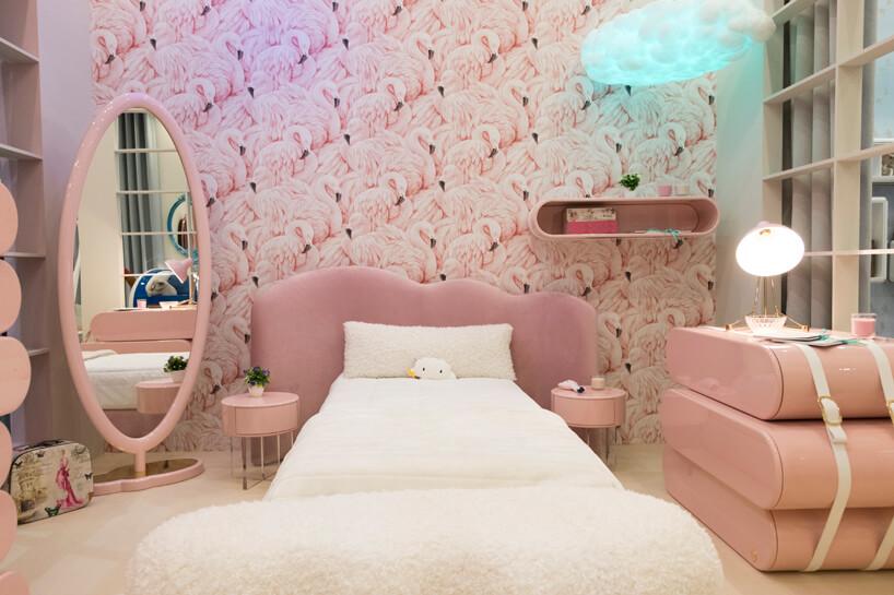 białe łóżko wróżowym pokoju dziecięcym zwysokim lustrem iróżową komodą