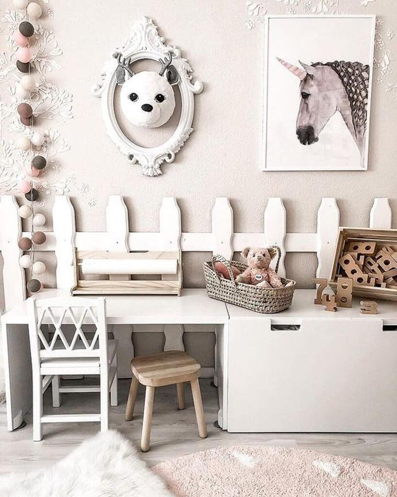 mały biały stolik ikrzesełko połączone zszafkami pod obrazkiem konia imałym płotkiem na ścianie
