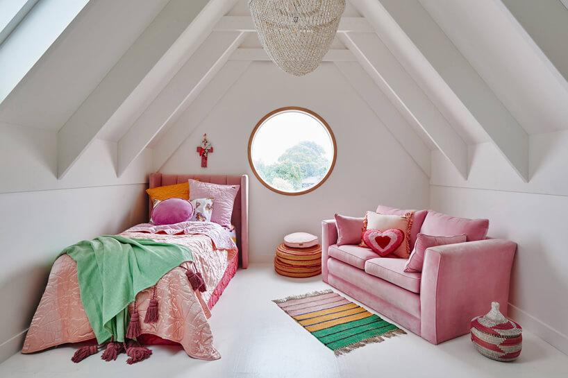 różowe łóżko isofa wpokoju dziecięcym dla dziewczynki na poddaszu