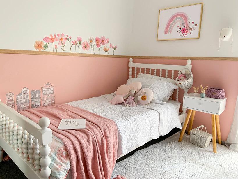 duże białe łóżko imały stolik na tle ózowej ściany inamalowanymi na niej kwiatkami
