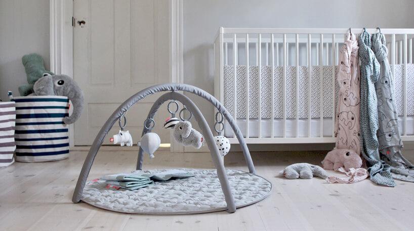 biały pokój dla niemowlaka zdrewnianym łóżeczkiem iszarą matą edukacyjną dla niemowlaka