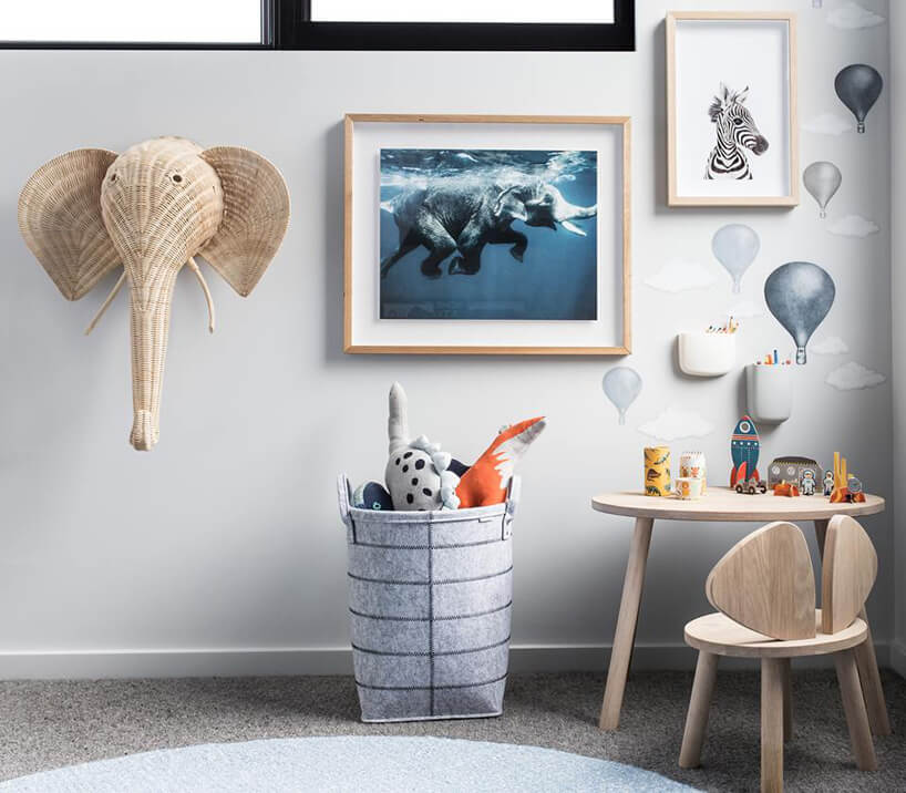 pokój dziecięcy zdrewnianym stolikiem ikrzesłem na tle ściany znamalowanymi balonami iobrazkami wramkach iwiklinową głową słonia