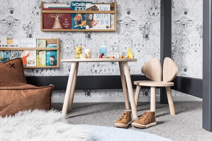 mały drewniany stolik ikrzesło wpokoju dziecięcym na tle szaro-białej tapety ze zwierzętami