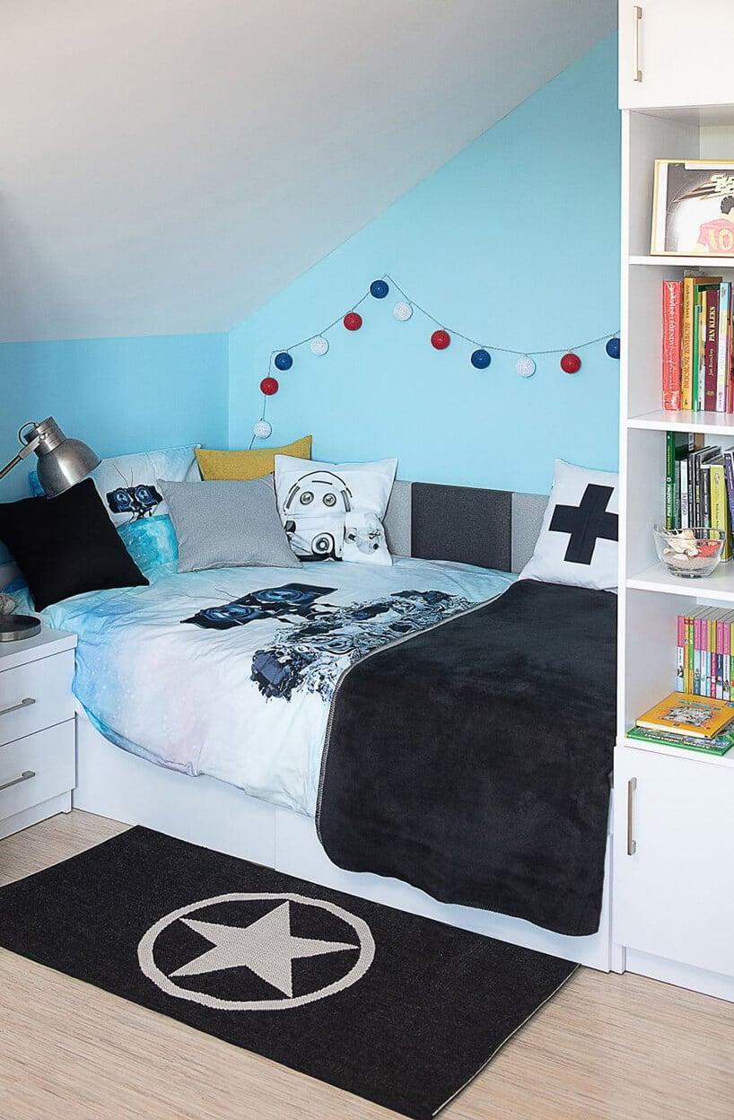 łóżko zczarnym kocem przy niebieskiej ścianie zkolorowymi kulkami na sznurku