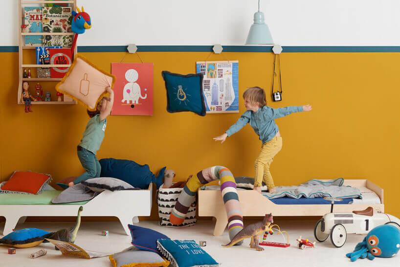 dwóch chłpoców bawiących się na łóżkach na tle pomarańczowej ściany