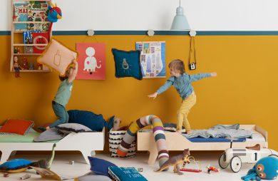 dwójka dzieci rzucająca się poduszkami na łóżkach w swoim pokoju