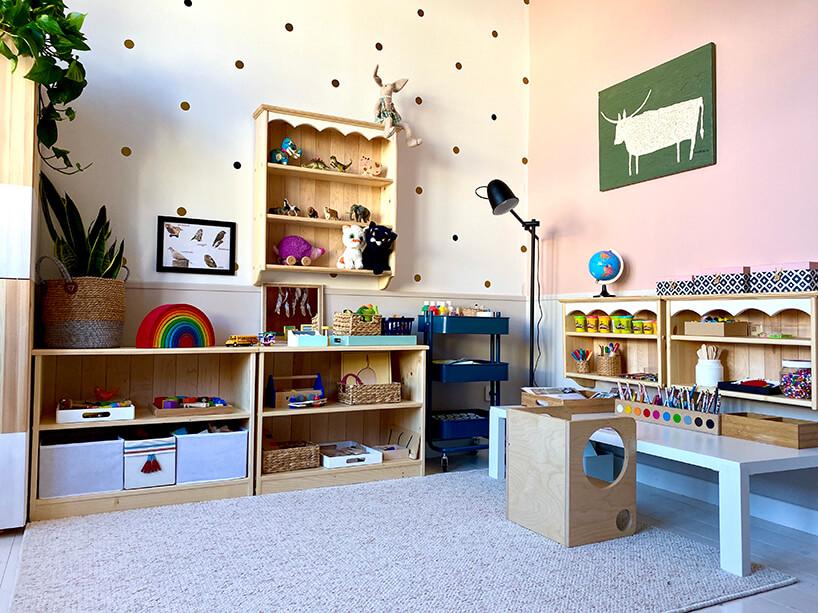 pokój dziecięcy wstylu Montessori od KUUDO drewniane szafki zzabawkami obok białego niskiego stolika