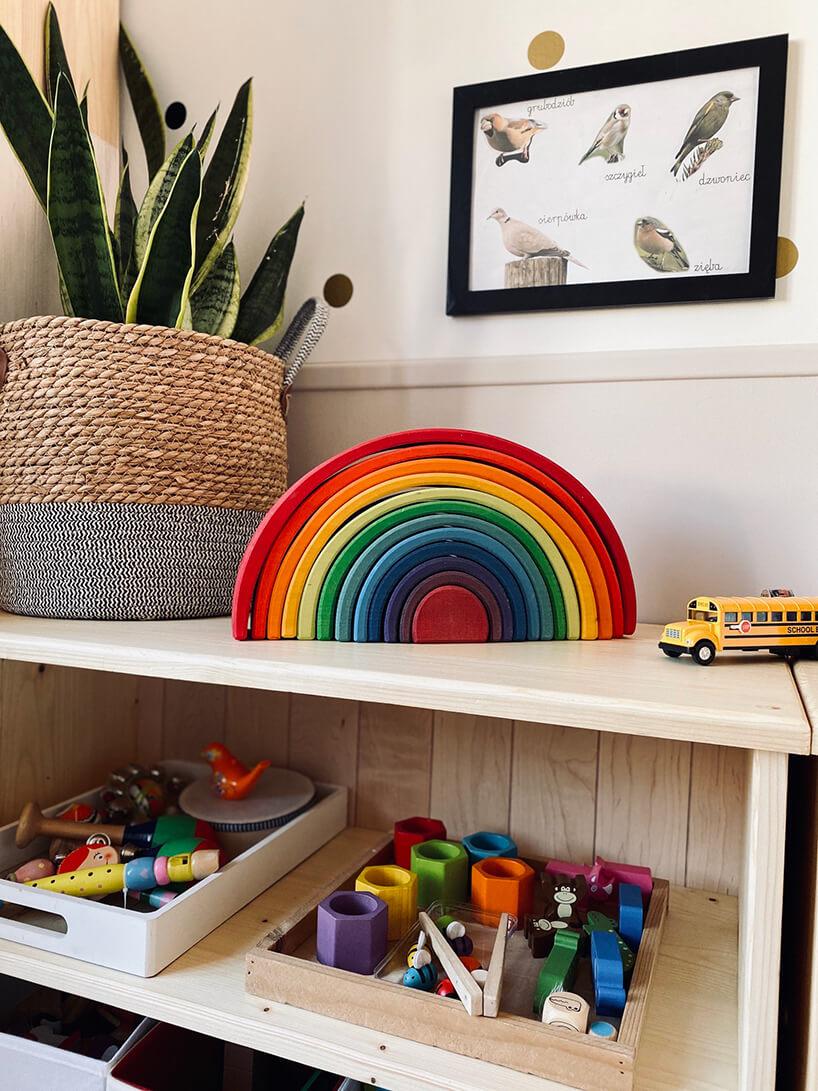 pokój dziecięcy wstylu Montessori od KUUDO drewniana szafka zzabawkami ikwiatem wosłonnej torbie znaturalnych materiałów