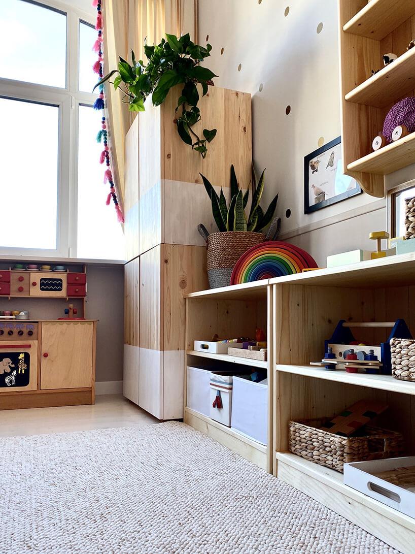 pokój dziecięcy wstylu Montessori od KUUDOdrewniana szafa obok rzędu szafek drewnianych zzabawkami idrewnianej kuchni do zabawy