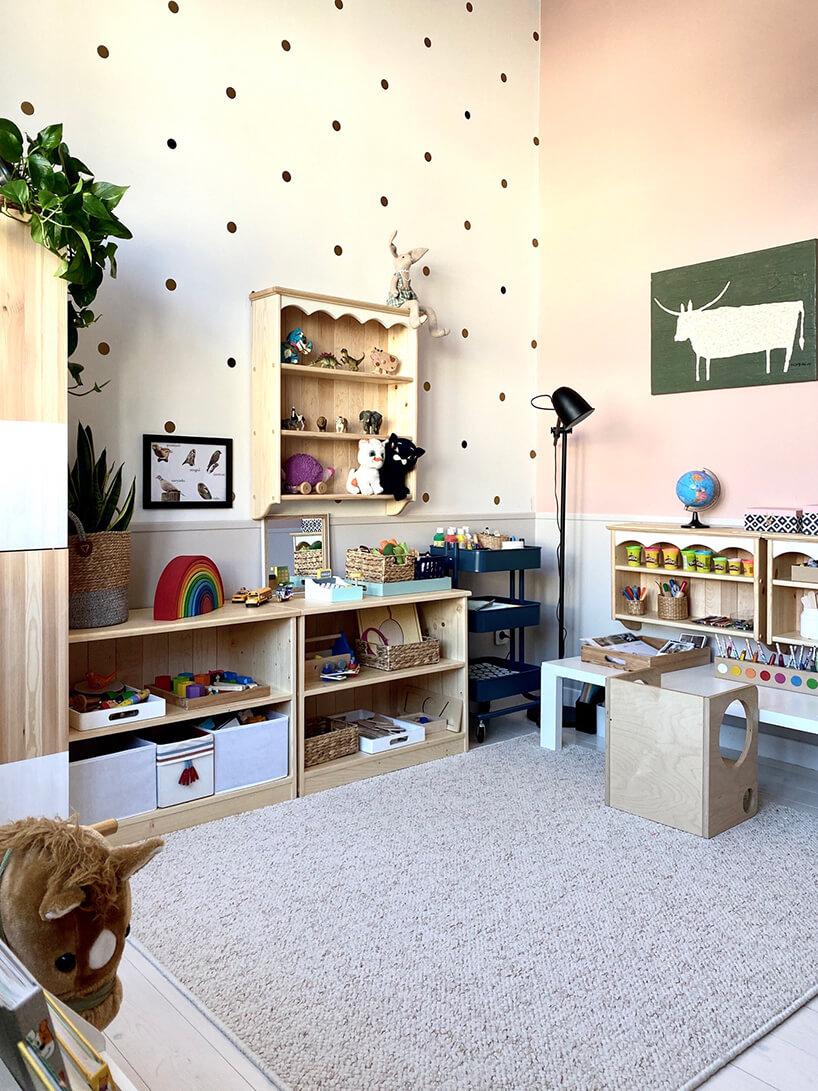 pokój dziecięcy wstylu Montessori od KUUDOdrewniane meble na zabawki wraz zwiszącą szafką na beżowej ścianie wkropki