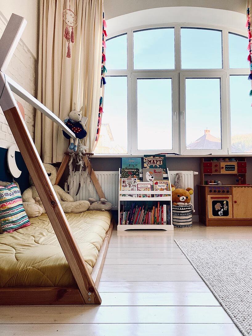 pokój dziecięcy wstylu Montessori od KUUDO drewniane łóżko zżółtym materacem na drewnianej podłodze obok małej białej szafki na na książki