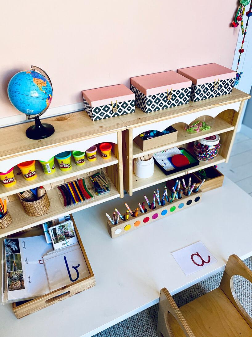 pokój dziecięcy wstylu Montessori od KUUDO dwie niskie drewniane szafki zkredkami iinnymi kreatywnymi rzeczami do zabawy