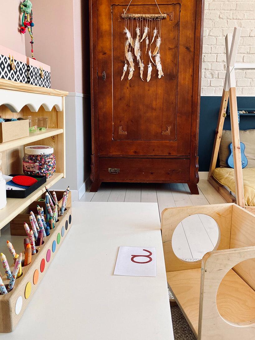 pokój dziecięcy wstylu Montessori od KUUDOmały drewniany stolik zdrewnianym podłużnym pojemnikiem na kredki na tle starej brązowej drewnianej szafy
