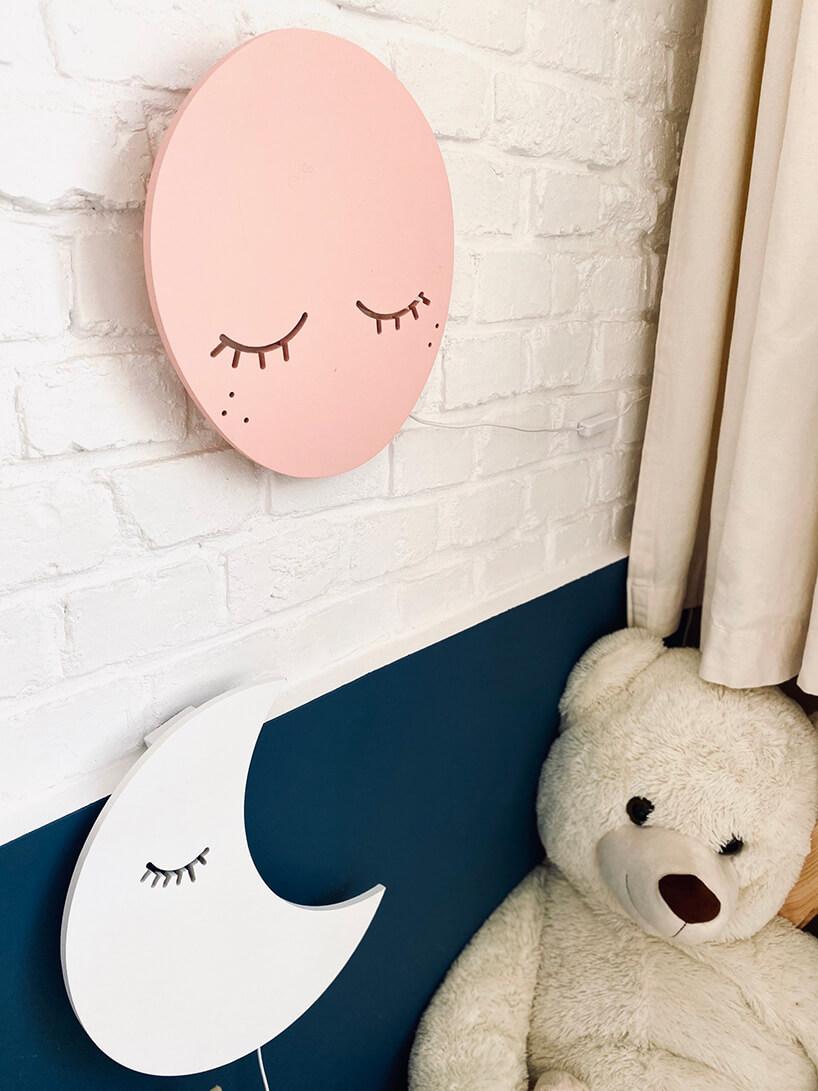pokój dziecięcy wstylu Montessori od KUUDOdwie wyjątkowe lampy wkształcie śpiącego księżyca na niebieskim tle isłońca na białej ścianie