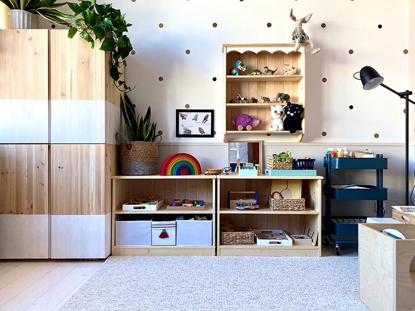 pokój dziecięcy wstylu Montessori od KUUDO drewniana szafa obok dwóch niskich drewnianych szafek na zabawki pod drewnianą wiszącą szafką zróżnymi figurkami dla dzieci