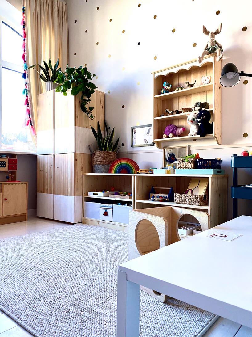 pokój dziecięcy wstylu Montessori od KUUDO szary dywan na drewnianej podłodze pomiędzy drewnianymi meblami dla dzieci