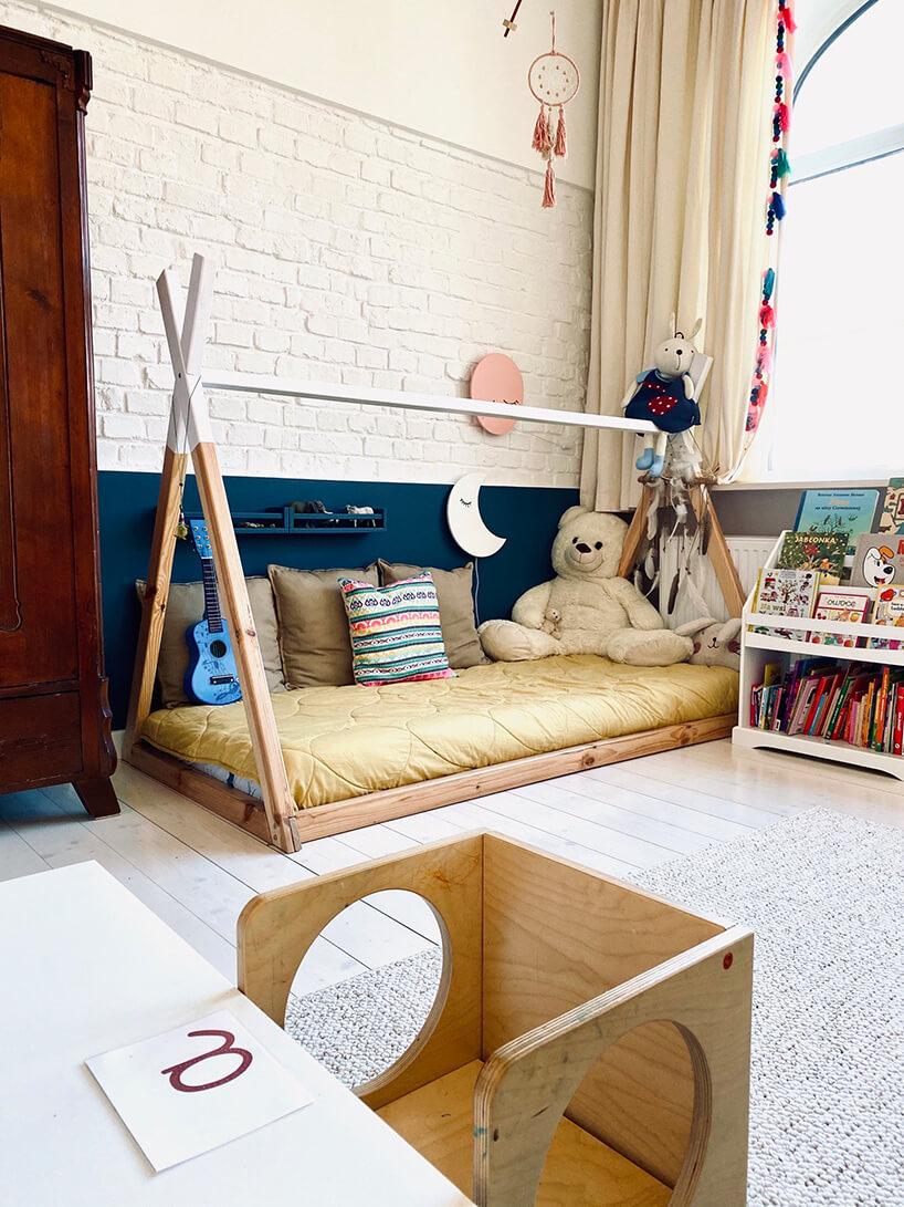 pokój dziecięcy wstylu Montessori od KUUDO drewniane łóżko dla dziecka wkształcie indiańskiego tipi na tle niebieskiej ibiałej ściany