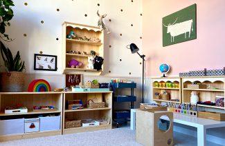 pokój dziecięcy w stylu Montessori od KUUDO drewniane szafki z zabawkami obok białego niskiego stolika