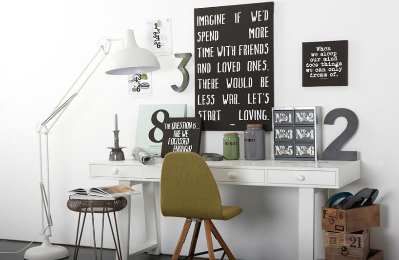 białe błyszczące biurko zzielonym krzesłem na drewnianych wysoką lampą podłogowa zregulacją iczarną tablicą na ścianie
