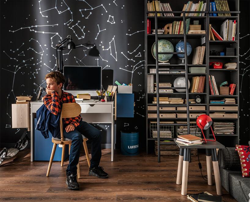 zestaw mebli dla ucznia od VOX biurko zkomputerem ora zwysoka szafką pełna książek na tle czarnej tapety zbiałymi gwiazdami