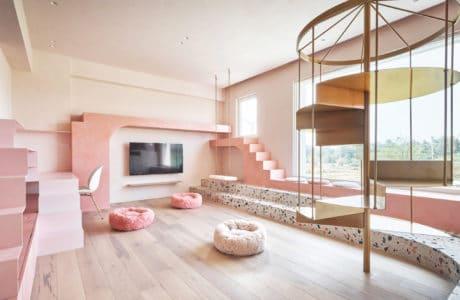 różowe wnętrze salonu ze złotymi kręconymi schodami