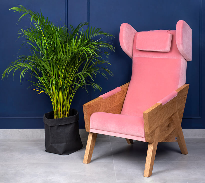 wysoki różowy fotel zdrewnianymi oparciami obok wysokiego kwiatka na tle niebieskiej ściany