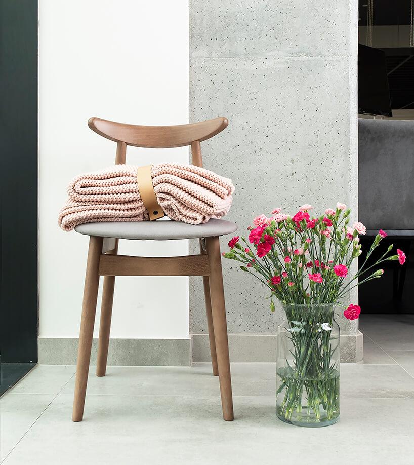 drewniane krzesło zjasnym siedziskiem na tle betonowej ściany
