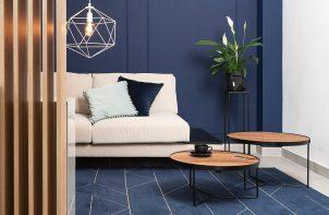 biała sofa obok dwóch okrągłych niskich stolików na niebieskim dywanie