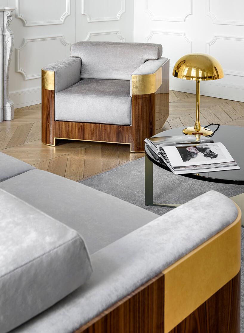 elegancki fotel od Atelier 1925 zszarym siedziskiem wykończony drewnem ze złotymi wstawkami obok okrągłego czarnego stolika ze złotą lampką