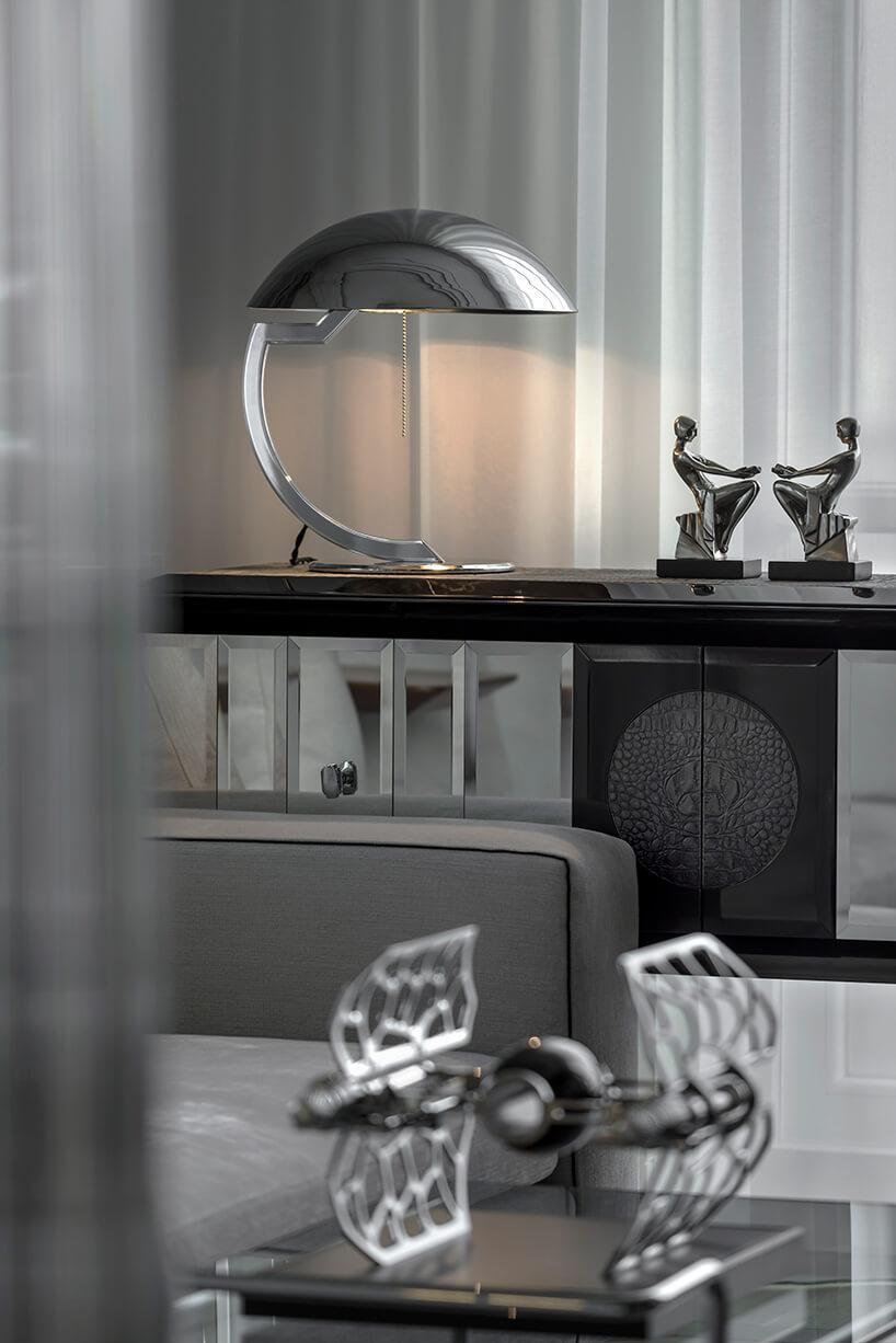 elegancka srebrna lampa na nowoczesnej komodzie ze szklanym idrewnianym wykończeniem