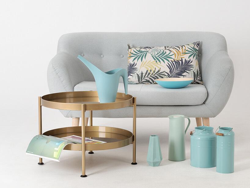 mała szara sofa jako tło dla różnych naczyń metalowych iporcelanowych obok okrągłego dwupoziomowego stolika