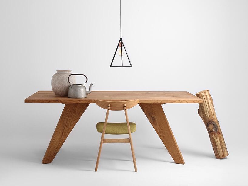 drewniany stół na drewnianych skośnych nogach pod prosta czarną lampą zmetalowych czarnych prętów