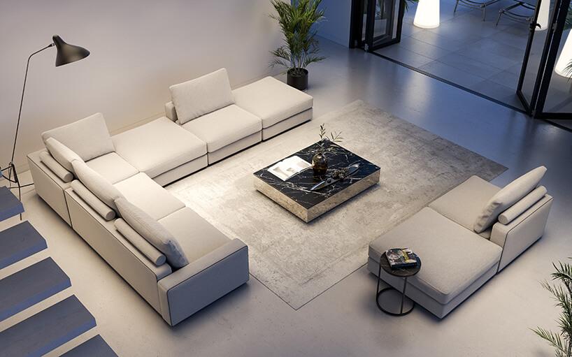 nowoczesne wnętrze zkamienną jasną podłogą zmodułowa narożną sofą przy czarnym kamiennym stoliku na szarym dywanie
