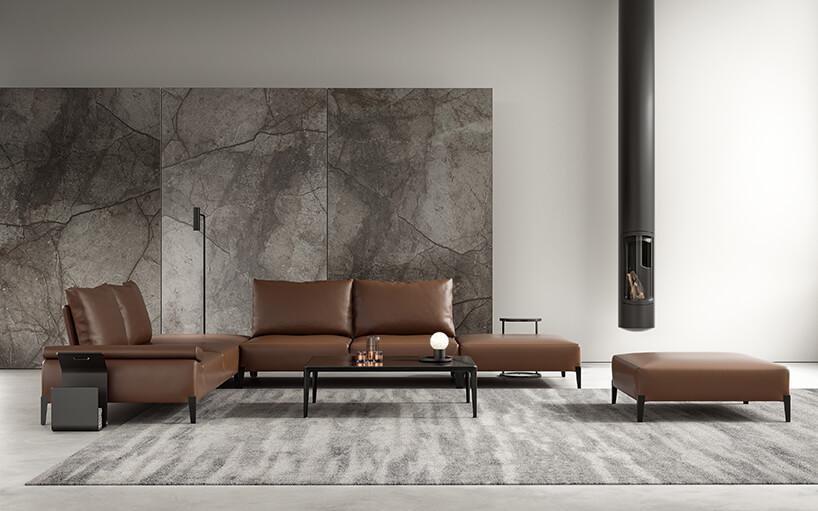 elegancka brązowa modułowa sofą na tle szarych kamiennych płyt obok podłużnego kominka