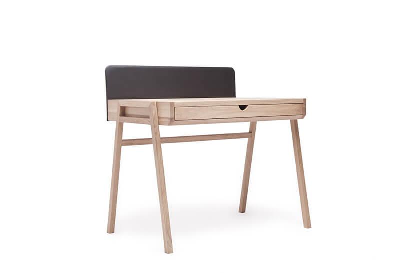 wyjątkowe małe drewniane biurko na drewnianych nogach zwmontowaną szufladą zczarną ścianką ztyłu