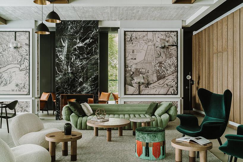eleganckie wnętrze zzieloną sofą przy drewnianych stolikach na tle ściany zgrafikami zelementami map śianką zczarnego kamienia