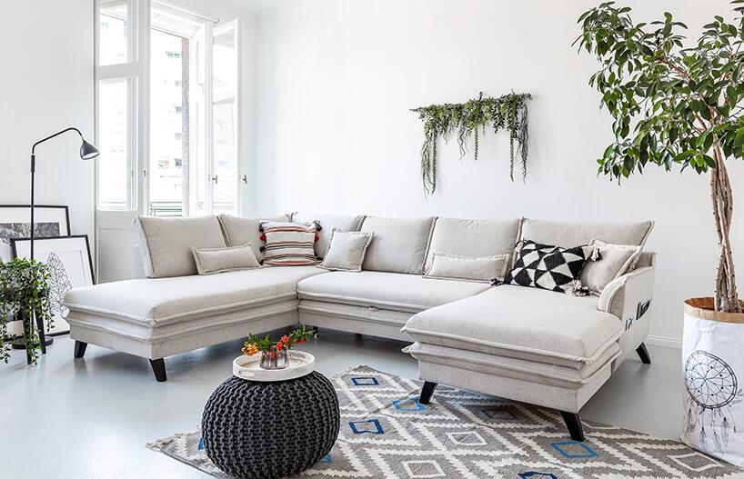 nowoczesna biała sofa narożna wbiałym wnętrzu