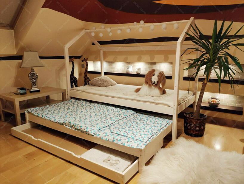 drewniane łóżko domek Bella złańcuchem świateł na górnej belce wpokoju dziecięcym na poddaszu