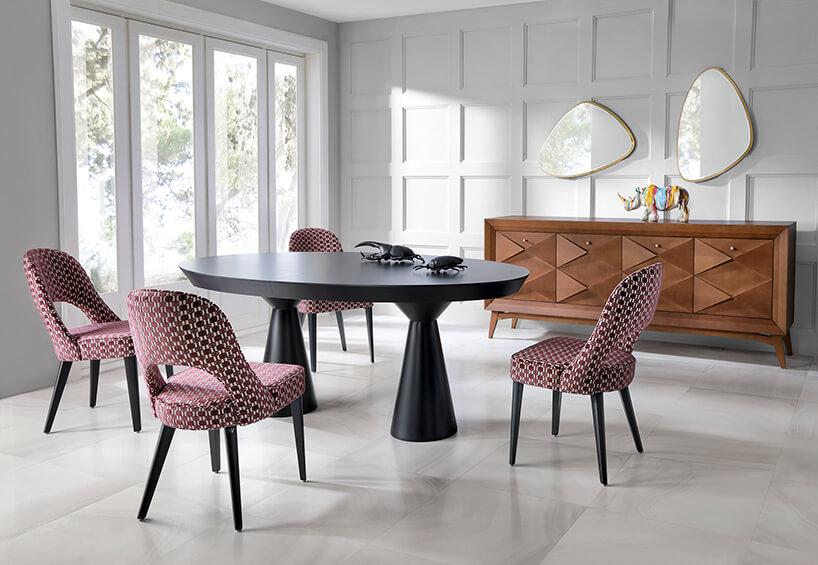 czarn stół na dwóch nogach pomiędzy czterema krzesłami zzbiało bordowymi wzorem na tle brązowej komody pod dwom lustrami onieregularnych zaokrąglonych kształatach