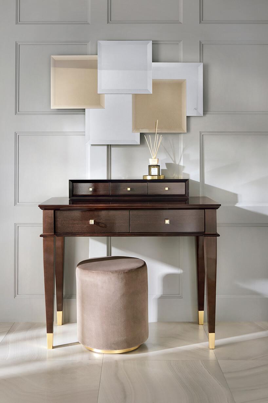 elegancki ciemno brązowy drewniany stolik ze złotymi okuciami na końcach zszarą pufą na złotej nodze