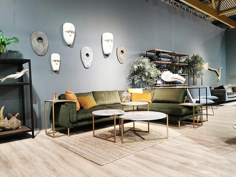 ciemno zielona sofa od Primavera Furniture zdosuwanymi stolikami nad siedzisko ioparcia