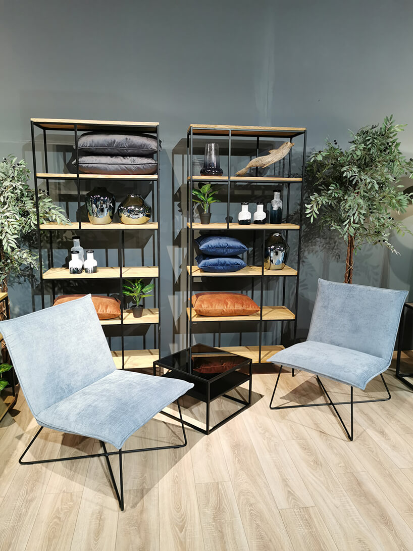 dwa niebieskie krzesła od Primavera Furniture przy małym czarnym stoliku ze szklanym czarnym blatem