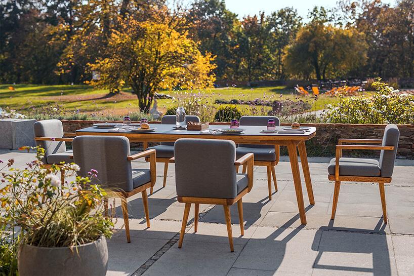 elegancki drewniany stół zszarym blatem zsześcioma drewnianym krzesłami zszarym siedziskiem ioparciem na tarasie na tle rozległego ogrodu