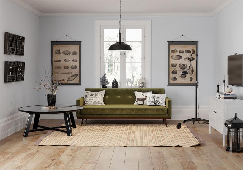 zielna sofa na drewnianych brązowych nogach wbiałym wnętrzu obok czarnego okrągłego niskiego stolika ze szklanym blatem