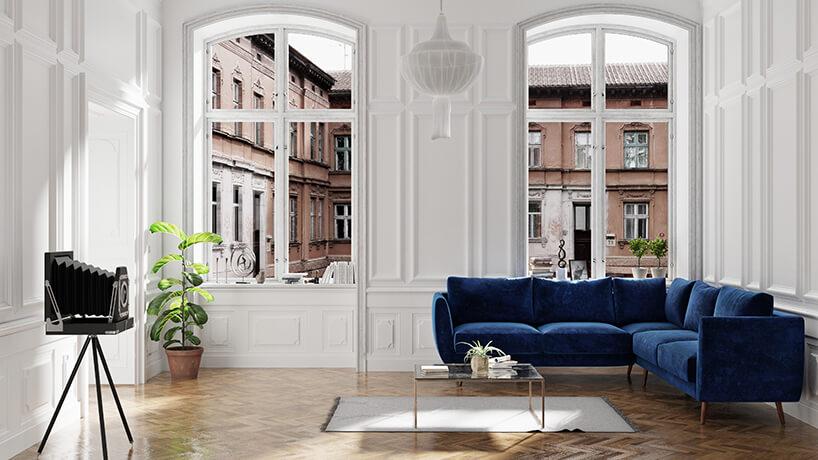elegancka ciemno niebieska sofa narożna od Scandisofa na tle starego okna zwidokiem na kamienice