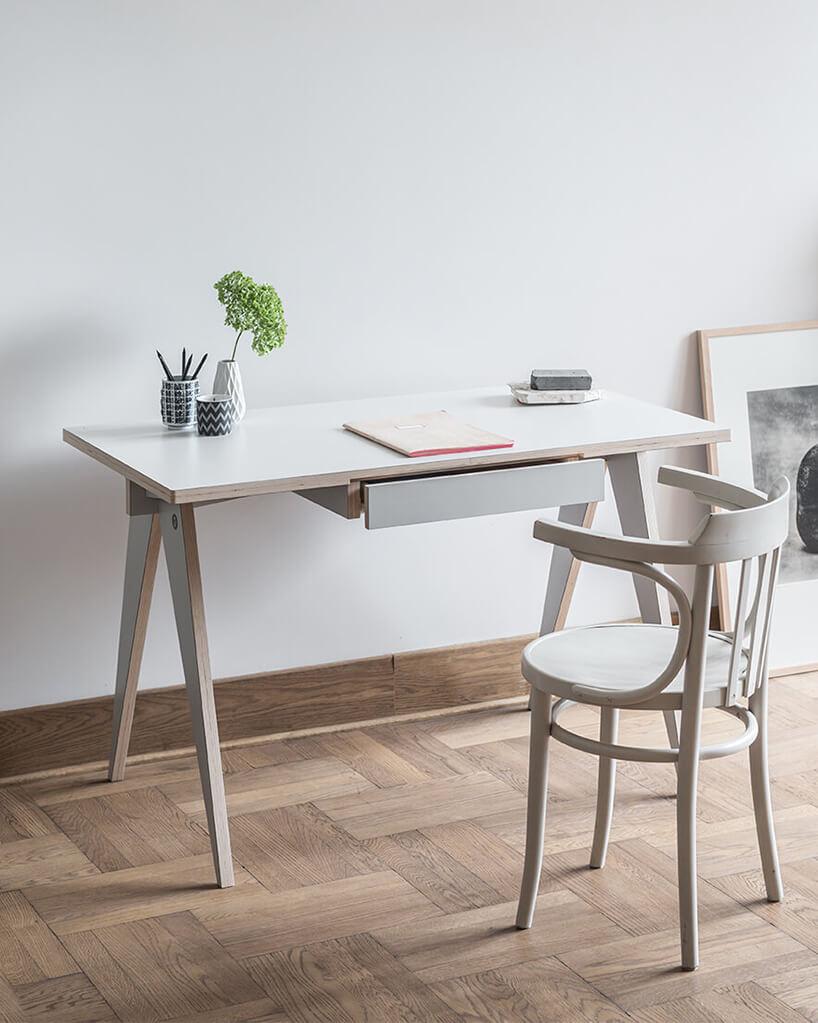 białe proste biurko zmałą szufladą po środku na drewnianym parkiecie od Swallow's Tail